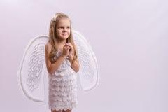 作为与翼的一个天使打扮的女孩折叠了手 免版税库存照片