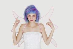 作为与被染的头发的天使打扮的愉快的少妇画象反对灰色背景 库存图片