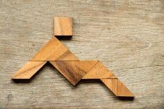 作为人的木七巧板难题坐或放下 免版税库存照片