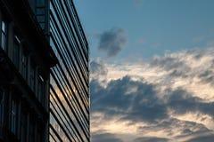 作为办公室地方使用的现代玻璃大厦在与一更旧修造的日落在它旁边 免版税库存照片
