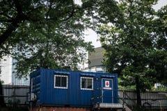 作为办公室的蓝色容器有绿色树的房子或房子作为背景 免版税库存图片