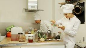 作为厨师和妇女打扮的男人准备食物 影视素材