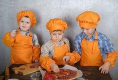 作为厨师打扮的三个逗人喜爱的欧洲男孩忙于烹调比萨 三个兄弟帮助我的母亲烹调比萨 免版税库存图片