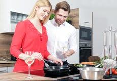 作为厨师的美好的性感的妇女人夫妇在厨房里烹调 免版税库存图片