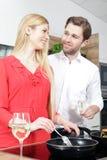 作为厨师的美好的性感的妇女人夫妇在厨房里烹调 免版税库存照片