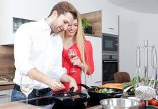 作为厨师的美好的性感的妇女人夫妇在厨房里烹调 图库摄影