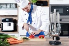 作为厨师的美好的性感的妇女人夫妇在厨房里烹调 免版税图库摄影