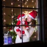 作为圣诞老人和婴孩打扮的母亲在圣诞节的一个窗口 库存照片
