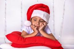作为圣诞老人打扮的一个小孩子预期圣诞节和新年 图库摄影