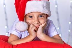 作为圣诞老人打扮的一个小孩子预期圣诞节和新年 库存图片