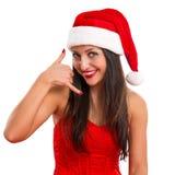 作为圣诞老人打扮的一名美丽的快乐的妇女的画象 免版税库存图片
