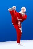 作为圣诞老人打扮的女孩做空手道反撞力 免版税库存照片