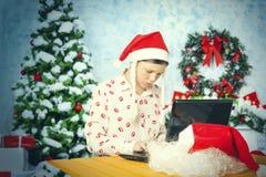 作为圣诞老人打扮的女孩在互联网上知道 免版税库存图片