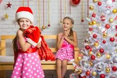 作为圣诞老人打扮的女孩带来了在袋子的礼物另一个女孩 库存照片