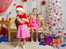 作为圣诞老人打扮的女孩带来了在袋子的礼物,另一个女孩高兴 库存照片