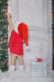 作为圣诞老人打扮的女孩开门在雪下 免版税库存图片