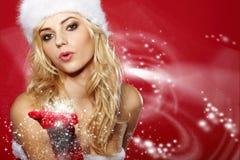 作为圣诞老人打扮的妇女吹在雪 免版税库存图片
