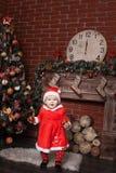 作为圣诞老人打扮的孩子在圣诞树附近 免版税库存图片