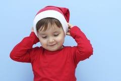 作为圣诞老人打扮的小孩投入圣诞老人帽子 免版税库存照片