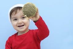 作为圣诞老人打扮的小孩显示一个金黄中看不中用的物品 库存图片