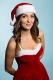 作为圣诞老人打扮的微笑的少妇 免版税库存照片