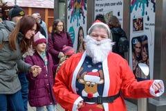 作为圣诞老人打扮的愉快的妇女在布里斯托尔圣诞节市场上 库存照片