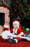 作为圣诞老人打扮的男婴坐与在他的韩的一把吉他 免版税库存照片