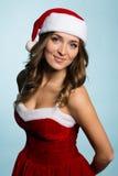 作为圣诞老人打扮的美丽的微笑的女孩 库存图片