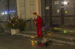作为圣诞老人打扮的街道音乐家弹萨克斯管 库存图片