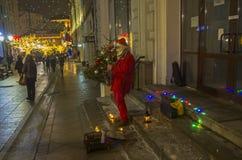 作为圣诞老人打扮的街道音乐家弹萨克斯管 库存照片