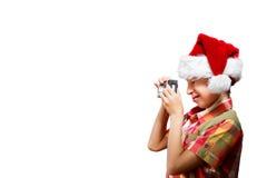 作为圣诞老人打扮的滑稽的小孩拍与照相机微笑的照片 库存图片
