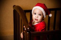作为圣诞老人穿戴的孩子在小儿床站立 免版税图库摄影