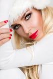 作为圣诞老人穿戴的美好的性感的白肤金发的女性模型 库存图片