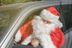 作为圣诞老人项目打扮的一个人交付在汽车的礼物 重音和路问题 免版税库存图片