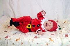 作为圣诞老人项目打扮的婴孩是淘气的在床上 库存照片