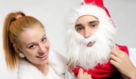 作为圣诞节和妇女的圣诞老人打扮的年轻人白色的 免版税库存照片