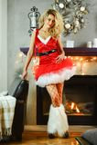 作为在摆在圣诞节的红色礼服和渔网袜子类的性感的圣诞老人帮手打扮的年轻美丽的白肤金发的妇女装饰了内部 免版税库存图片