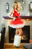 作为在摆在圣诞节的红色礼服和渔网袜子类的性感的圣诞老人帮手打扮的年轻美丽的白肤金发的妇女装饰了内部 图库摄影