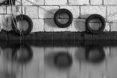 作为在海船坞的防撞器使用的老汽车轮胎 库存照片