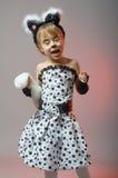 作为在灰色背景的一只猫打扮的可爱的小女孩 免版税库存图片