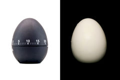 作为在白色背景隔绝的一个黑鸡蛋和煮沸的被剥皮的鸡蛋的定时器在黑色 免版税库存照片