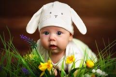 作为在草的复活节兔子兔子打扮的愉快的儿童婴孩 免版税库存照片