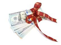 作为在w的一件礼物栓与红色丝带和装饰的美金 库存图片