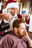 作为大师的圣诞老人在理发店 免版税库存图片