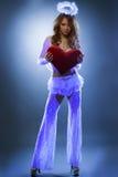 作为天使打扮的性感的女孩摆在紫外光下 免版税库存图片