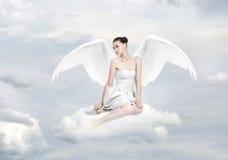 作为天使的美丽的少妇坐云彩 免版税库存图片