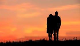 作为夫妇现出轮廓日出日落 免版税库存图片