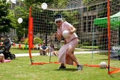 作为女王伊丽莎白打扮的人扮演足球守门员 库存图片