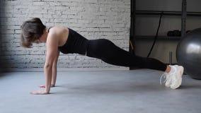 作为她的发怒健身,建身的健身房训练惯例一部分,这录影是关于运动美女做俯卧撑 影视素材