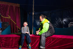 作为小丑打扮的男孩坐与人的阶段 免版税库存照片